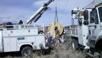Photograph: two large white utility trucks occupy the foreground. In the background, two workers handle a large spool of cable.