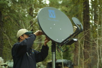 Photograph: a technician works on a WildBlue satellite internet dish. Trees fill the background with greenery.