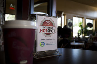 Photograph: Inside a coffee shop, a to go beverage cup stands in front of a small sign advertising the presence of a PST Wi-Fi Hotspot.